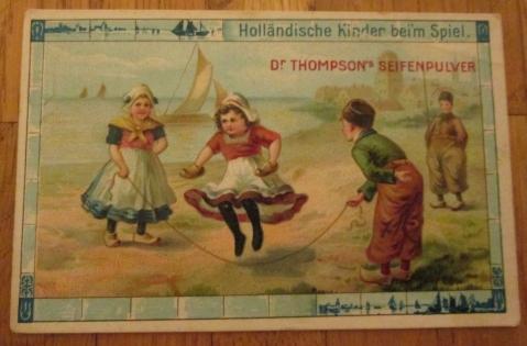 """Eine der Karten in Nahaufnahme. Sichtbar ist, dass die Konzeption einer Serien immer einen Stil, mit sich wiederholendem Bildaufbau (hier immer wieder die gleichen Kinder in gleicher """"landestypischer"""" Kleidung) und Schmuckelementen (hier die Kacheln am Rand, die einen niederländisch-norddeutschen Stil aufgreifen) beinhaltete. Für einfache Karten, die offenbar kostenlos verteilt wurden, ist die Qualität der Bilder recht gut, obgleich sich Stile mit der Zeit wiederholen. Es wird zum Beispiel auf Kleinigkeiten im Hintergrund geachtet."""