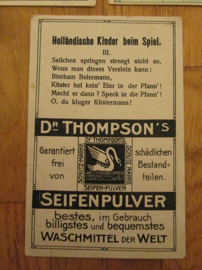 """Hier die Rückseite der gleichen Karte mit einem typischen Aufbau. Einerseits ein Text, der sich auf das Bild bezieht, hier ein Gedicht über das Spiel der Kinder in Holland. Die anderen vier Karten haben ähnliche Gedichte und sind von I. bis V. durchnummeriert (ob es einen sechste Karte gab weiss ich nicht). Dieser Text vermittelt keine wirklichen Inhalte, die finden sich aber bei anderen Serien. Andererseits enthält die Rückseite Werbung für das Produkt """"Dr Thompson's Seifenpulver"""", inklusive Markenlogo. Dabei bezog sich die Werbung offenbar nicht auf den anderen Inhalt der Karte. Zumindest bei den Karten, die ich gesehen habe, wurden Werbetexte immer wieder verwendet, wenn auch die Texte auf der jeweiligen Karte teilweise dem vorhanden Platz angepasst wurden."""